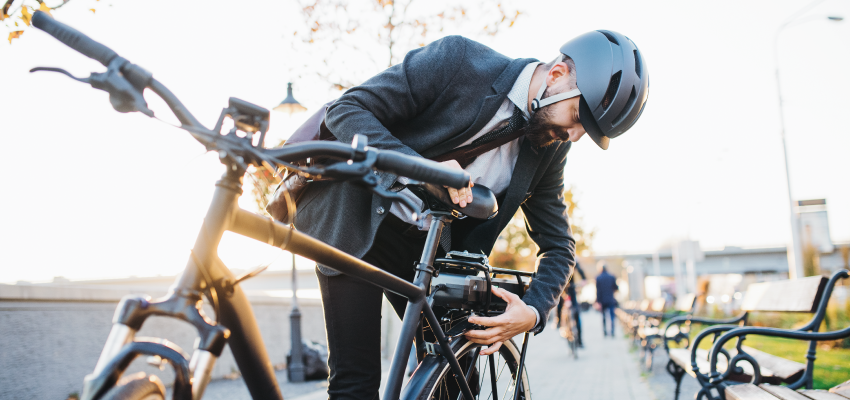 Man met fietshelm die batterij aanzet op fiets
