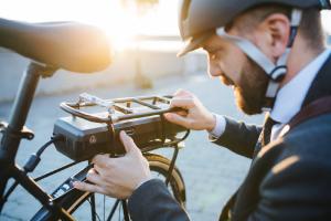 Man die batterij van zijn elektrische fiets nakijkt