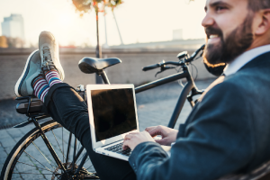 Man die op zijn laptop zit bij de fiets
