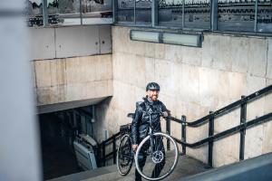 man die de trappen opgaat met zijn fiets